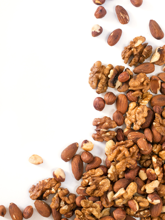 Background of mixed nuts - hazelnuts, walnuts, almonds - with copy space. Isolated one edge. Top view or flat lay. Vertical image