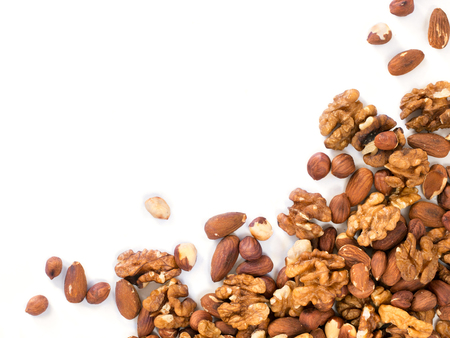 Background of mixed nuts - hazelnuts, walnuts, almonds - with copy space. Isolated one edge. Top view or flat lay