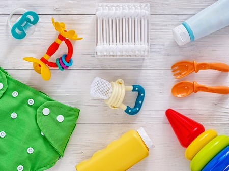 teether: Collection of items for babies: cloth diaper, baby powder, nibbler, cream, teether, soother, cotton swabs, baby spoon and fork, pyramid toy on white wooden background. Top view or flat lay