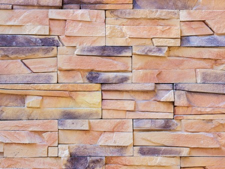 decorate: a wall from an artificial beige and gray stone facade with rough fractured surfaces