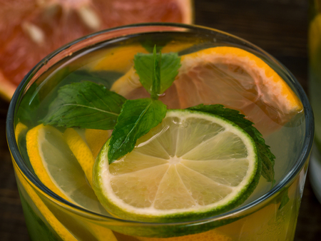 Close up cold homemade lemonade with fresh lemon, lime, grapefruit and mint. Summer drink on dark wooden background