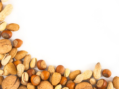 mixed nuts: Background of mixed nuts in shell - hazelnuts, almonds, walnuts, pistachios, peanuts not peeled - with copy space. Isolated one edge. Top view or flat lay Stock Photo