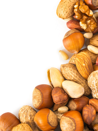 pine kernels: Background of mixed nuts - hazelnuts, almonds, walnuts, pistachios, peanuts, pine nuts peeled and not peeled - vertical with copy space. Isolated one edge. Top view or flat lay