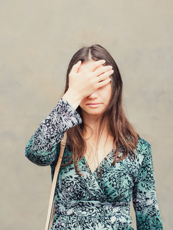 conspiratorial: facepalm girl. Portrait of young woman doing facepalm posing against gray wall background. Vertical Stock Photo