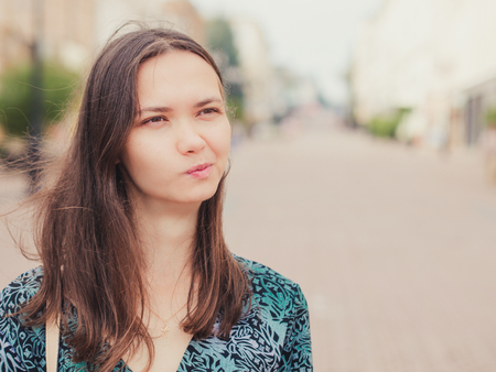 aggravated: displeased handsome young woman looking away outdoors with copy space Stock Photo