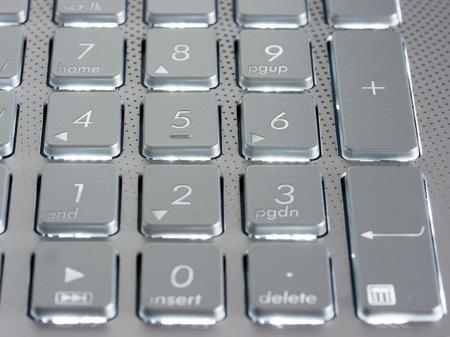 dof: Number keys on silver keyboard of laptop, close up, horizontal image. Shallow DOF
