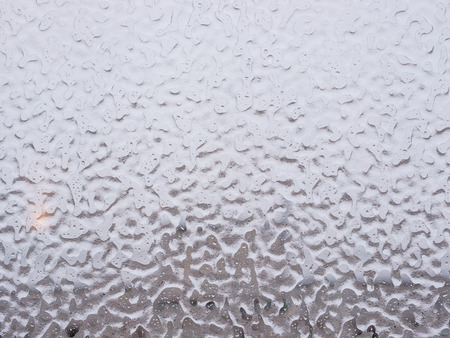 inclement weather: Texture of ice and drops on window glass in inclement winter weather. Close up. Icy rain background