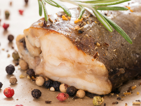Steamed Fish with fresh rosemary and peppercorns close up. Healthy food.