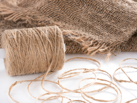 natural rope: Skein of jute twine. Clew of natural rope. Roll of twine jute on sacking Stock Photo