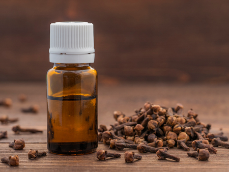 Spice clove essential oil in dark glass bottle anddry cloves on dark wooden background with copy space