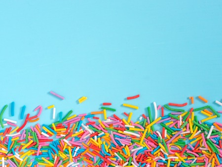 Border frame of colorful sprinkles on blue background