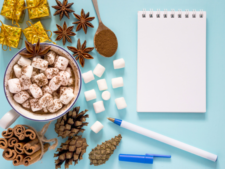 Cup of hot cocoa or carob or chocolate with marshmallow and winter spices star anise and cinnamon sticks, pine cones and carob powder in spoon and gifts and empty notebook on turquoise table. Flat lay Stock Photo