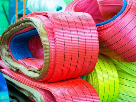 backstitch: Colorful nylon soft lifting slings stacked in piles. Warehouse of finished products for industrial enterprises Stock Photo