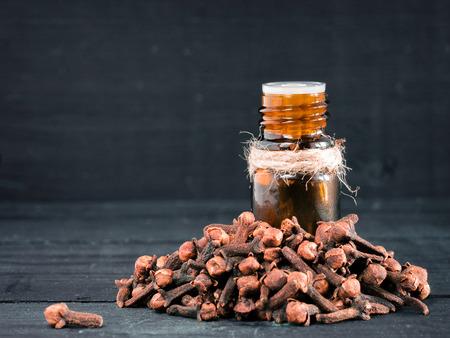 スパイスは、コピー領域と暗い背景の木に暗いガラスの瓶や乾燥のクローブの精油をクローブ