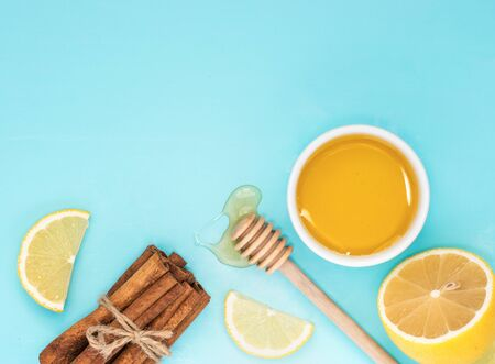 cerulean: Lemon, honey and cinnamon sticks on turquoise blue background with copy space. Top view or flat lay. Stock Photo