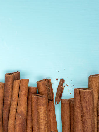 cerulean: Cinnamon sticks on turquoise blue background with copy space. Top view or flat lay. Vertical
