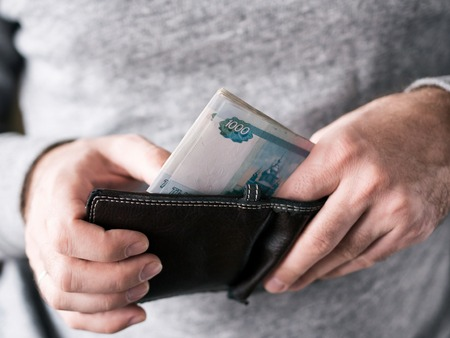 depreciation: Hands take out russian rubles from wallet. Closeup on a mans hands as he is getting a banknote out of his wallet