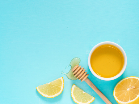 cerulean: Lemon and honey on turquoise blue background with copy space. Top view or flat lay. Stock Photo