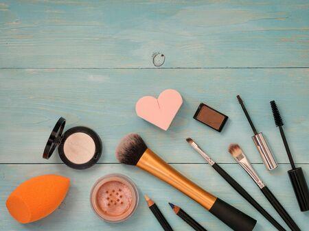 cerulean: Set of make up on turquoise wooden background. Mascara brush, eyebrow gel brush, pencil, eyeshadow, sponge and brushes. Mock up with copyspace. Shallow DOF Stock Photo