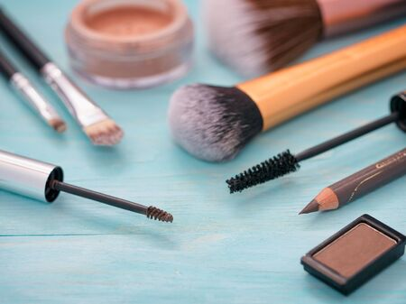 cerulean: eyebrow gel or mascara brush and other makeup set on turquoise wooden background. Stock Photo