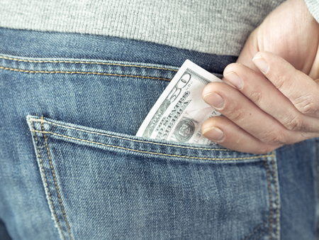 hand put dollars in jeans pocket Stock Photo