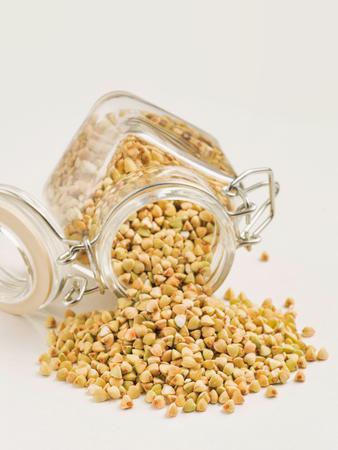 Raw green buckwheat in bank on white background