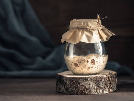 Active rye sourdough starter in glass jar on brown wooden background. Starter for sourdough bread. Toned image. Copy space. Stock Photo