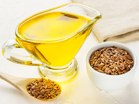 Brown flax seeds in spoon and flaxseed oil in glass jug on trendy textured white concrete background. Flax oil is rich in omega-3 fatty acid. Stock Photo