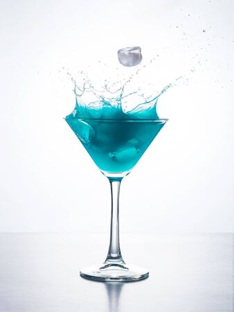 stirred: Blue cocktail in martini glass with ice cube splashing into liquid against white background. Blue curacao cocktail with splash on white.