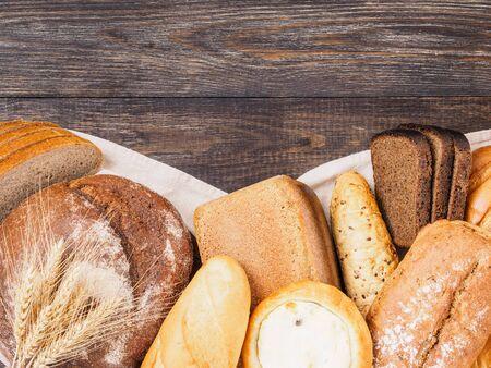 茶色の木製の背景にパンの品揃え