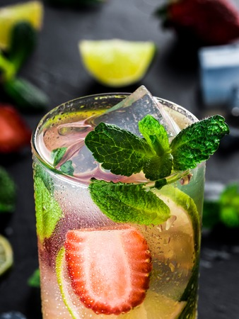 fresh lemonade with strawberry, lime and mint on dark stone background. Cold summer strawberry drink with mint and ice. Strawberry mojito in glass and ingredients. Vertical
