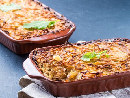 browned: Close up view of appetizing potato casserole with fish, eggs and cream. Potato casserole in serving baking dish on dark concrete background