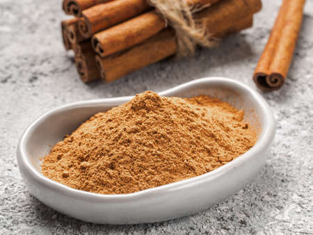 Close up view of ground cinnamon in trendy plate and cinnamon sticks on gray cement background Stock Photo