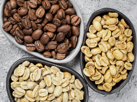 unroasted: Trendy plates with white, green and brown coffee bean on gray concrete background. Top view or flat lay. Image with natural colors Stock Photo