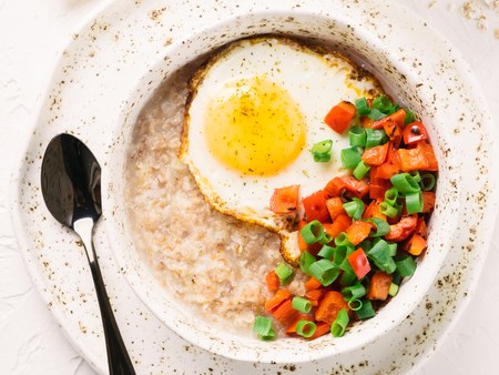 Savory oatmeal, served with vegetables and fried egg Stock Photo
