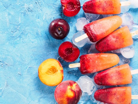 top view of plum and peach popsicle on blue background with copyspace