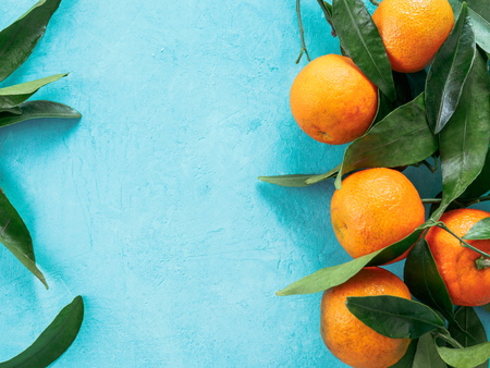 Tangerines, oranges, mandarins, clementines, citrus fruits with leaves on blue concrete background. Top view or flat-lay. Copy space. Stock fotó