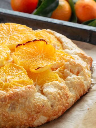 clementines: Close up view of caraway and orange tart in baking tray. Winter season and christmas ideas recipe - tart with caraway pastry and oranges, mandarines or tangerines. Stock Photo