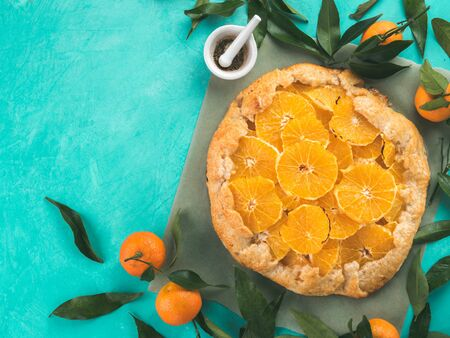 cerulean: Top view of caraway and orange tart on baking paper over blue concrete background with copy space.Winter season and christmas ideas recipe-tart with caraway pastry and oranges,mandarines or tangerines