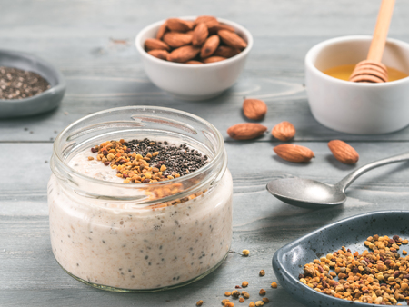 Overnight oats in jar and ingredients on gray wooden table Stock Photo