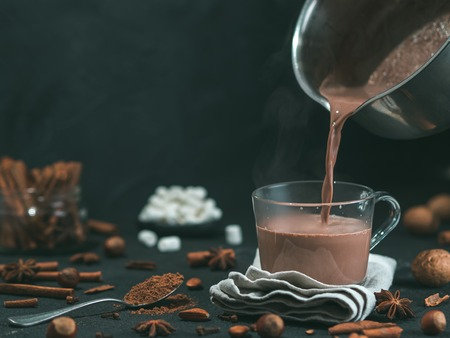 Pouring tasty hot chocolate cocoa drink into glass mug with ingredients on black table. Copy space Dark background. Low key.