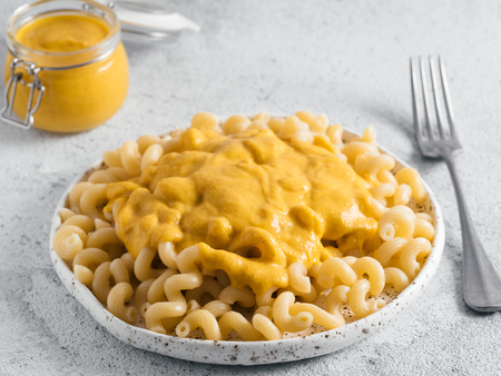 Pasta with vegan creamy chia cheddar sauce on gray background. Ideas and recipe for healthy diet or vegan food. Dish with homemade plant based Chia Cheeze Sauce. Copy space