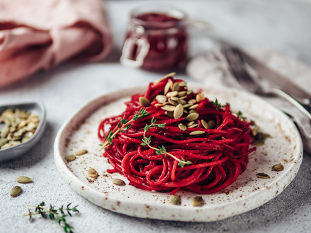 Roasted beetroot and thyme spaghetti with pumpkin seed in craft plate on gray cement background. Ideas and recipes for healthy vegan vegetarian dinner. Selective focus. Imagens