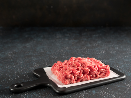 Fresh raw minced beef on backing paper and cutting board over black cement background with copy space. Stock fotó