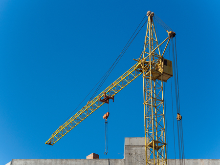 working yellow crane with the blue sky on the background Standard-Bild