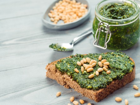 Close up view of whole grain rye bread with fresh basil pesto sauce on gray wooden table. Copy space.