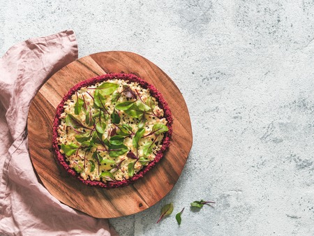 beetroot pizza crust with fresh swiss chard or mangold beetroot leaves.Ideas and recipes for healthy vegan snack.Egg-free pizza crust with chia seed and wholegrain brown rice flour.Copy space.Top view