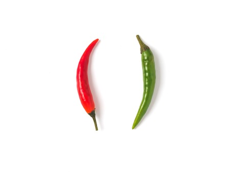 Creative layout chilli peppers. Two peppers - green and red hot pepper, isolated on white with clipping path. Copy space for text. Top view or flat lay.
