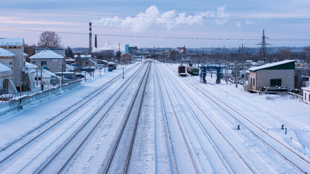 Winter view of empty railway station. Tracks without trains and white snow between them. Stock Photo
