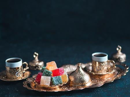 Café turco con delicia y servicio de cobre tradicional sobre fondo oscuro. Surtido de dilight turco tradicional o lokum y café turco en tazas tradicionales de metal. Espacio de copia. El enfoque selectivo